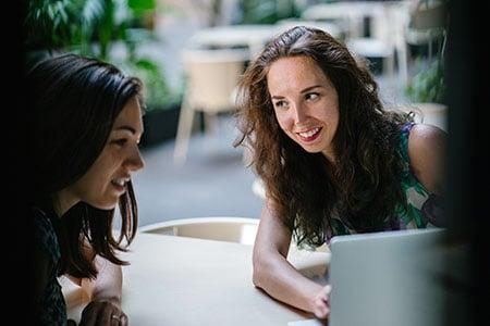 two-talking-women-while-using-laptop-1311547