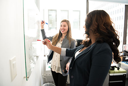 two-women-in-front-of-dry-erase-board-1181533